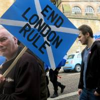 A demonstrator carries a sign during a pro-independence march in Edinburgh, Scotland, on March 15. A Sept. 18 referendum is soon to determine whether Scotland becomes independent of the United Kingdom. | AP