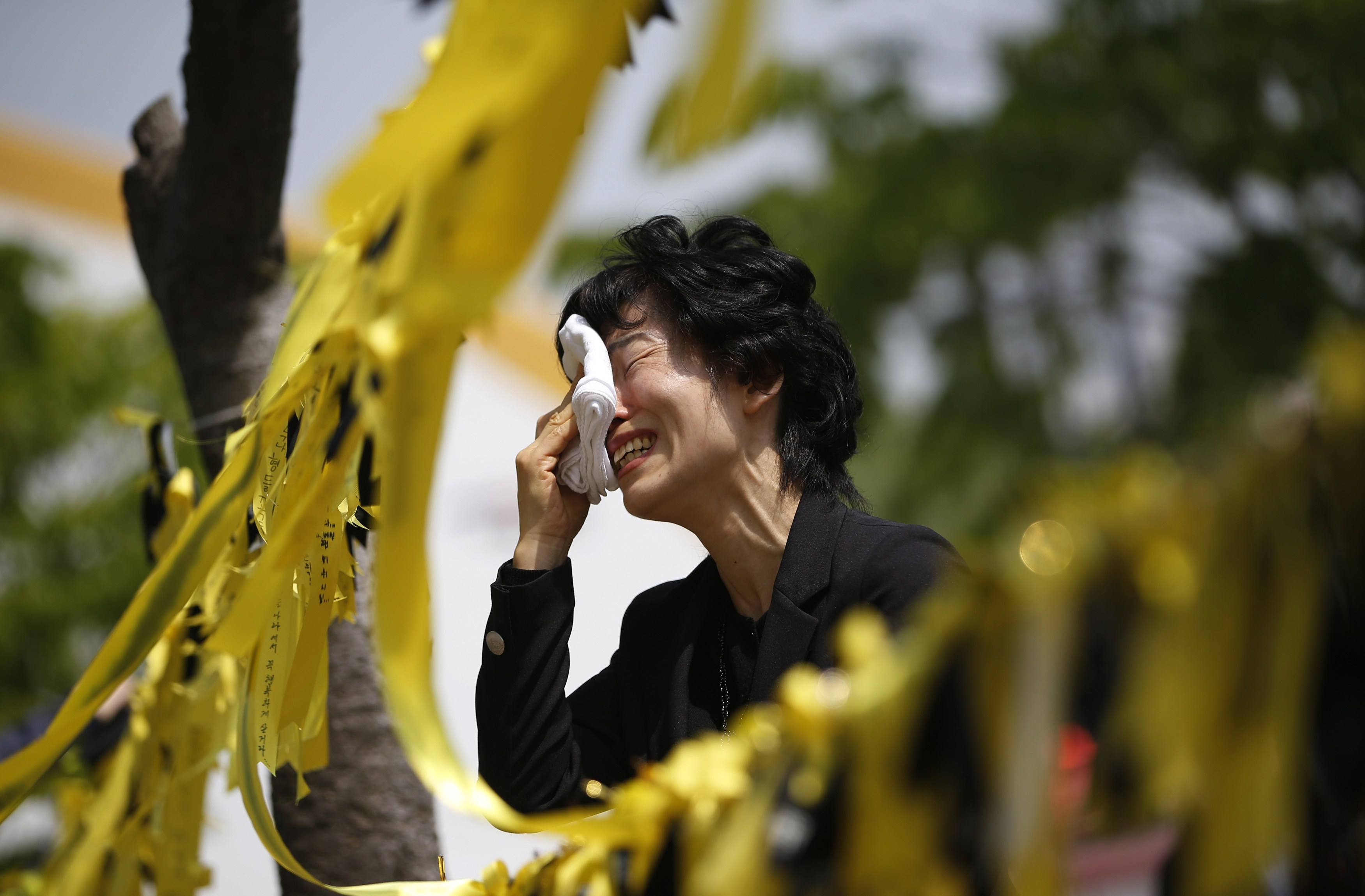 A mourner cries next to yellow ribbons dedicated to missing and dead passengers of the sunken Sewol passenger ship at the official memorial altar in Ansan, South Korea, on May 2. | REUTERS