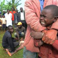 A boy cries before going under the scalpel Friday in Shinyalu, near Kenya's Kakamega National Park. It is carried out without anaesthetic and is considered a rite of passage for boys aged 10 to 18. Outsiders avoid the Bukusu tribe whenever its knives are out. | AFP-JIJI
