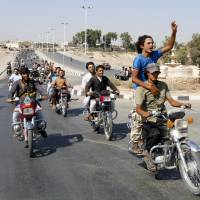 Residents from the city of Tabqa ride alongside Islamic State militants in a celebratory tour of the streets after the Sunni militants wrested control of Tabqa air base from Syrian government forces on Sunday. Their victory came after days of fighting over the strategic location, which was the Syrian army's last foothold in northeast Syria. | REUTERS