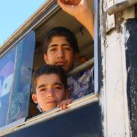 Syrians sit on a bus heading to the southern Damascus district of Qadam on Thursday as they return to their homes after authorities and rebels agreed to a truce earlier last week. The Syrian Army has never managed to take the district that has been held by various rebel factions, with the exception of the jihadists of the Islamic State. | AFP-JIJI