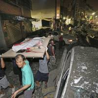 A victim killed in a gas explosion from an underground gas leak is carried from the rubble in a main street in Kaohsiung, Taiwan, early Friday.   AP