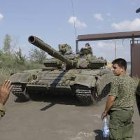 Pro-Russian rebels park a tank at their base near the town of Krasnodon in eastern Ukraine on Saturday. Tanks and armored personnel carriers continued to maneuver on the Ukrainian side of the border on Saturday, and a 280-truck Russian aid convoy waited on the other side. | AP