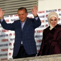 Turkey's Prime Minister Tayyip Erdogan and wife Ermine wave hands to supporters as they celebrate his election victory in front of the party headquarters in Ankara. Erdogan secured his place in history as Turkey's first directly elected president on Sunday, sweeping more than half the vote in a result his opponents fear heralds an increasingly authoritarian state. | REUTERS