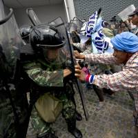Thai farmers battle with soldiers during a February protest over the government's repeatedly delayed payments for rice submitted to the pledging system in Bangkok. | AFP-JIJI