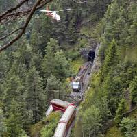 A helicopter flies over a train after it was derailed by a landslide near Tiefencastel, in a mountainous part of eastern Switzerland, on Wednesday. | AFP-JIJI
