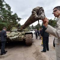 A military attache examines a Russian T-64BV tank displayed in Kiev on Friday. | AFP-JIJI