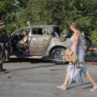 A woman passes by members of the Ukrainian self-defense battalion Donbass near the town of Pervomaysk on Thursday. Ukraine said it had suspended offensive operations in its military campaign in east Ukraine to help international experts reach the downed Malaysian airliner's crash site, but separatists were continuing to attack its positions. | REUTERS