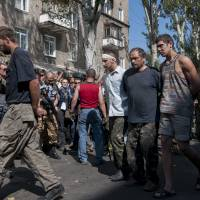 Pro-Russian rebels escort captured Ukrainian army prisoners in a central square in Donetsk, eastern Ukraine, Sunday. Ukraine has retaken control of much of its eastern territory bordering Russia in the last few weeks, but fierce fighting for the rebel-held cities of Donetsk and Luhansk persists. | AP
