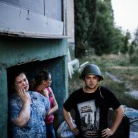People stand at the entrance of a makeshift bomb shelter in Donetsk on Sunday. Artillery pounded the main rebel bastion of Donetsk, which is surrounded by Ukrainian forces, as the West warned Russia that any attempt to send 'humanitarian' troops into the conflict-torn region would be deemed 'unacceptable.' | AFP-JIJI