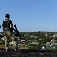Ukrainian loyalist fighters from the Azov Battalion stand guard on a hill on the outskirts of they key port city of Mariupol, in Ukraine's east, on Saturday. | AFP-JIJI