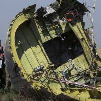 Members of a group of international experts on Friday inspect wreckage at the site near the village of Hrabove, in eastern Ukraine's Donetsk region, where the downed Malaysia Airlines Flight MH17 crashed to Earth in mid-July. | REUTERS