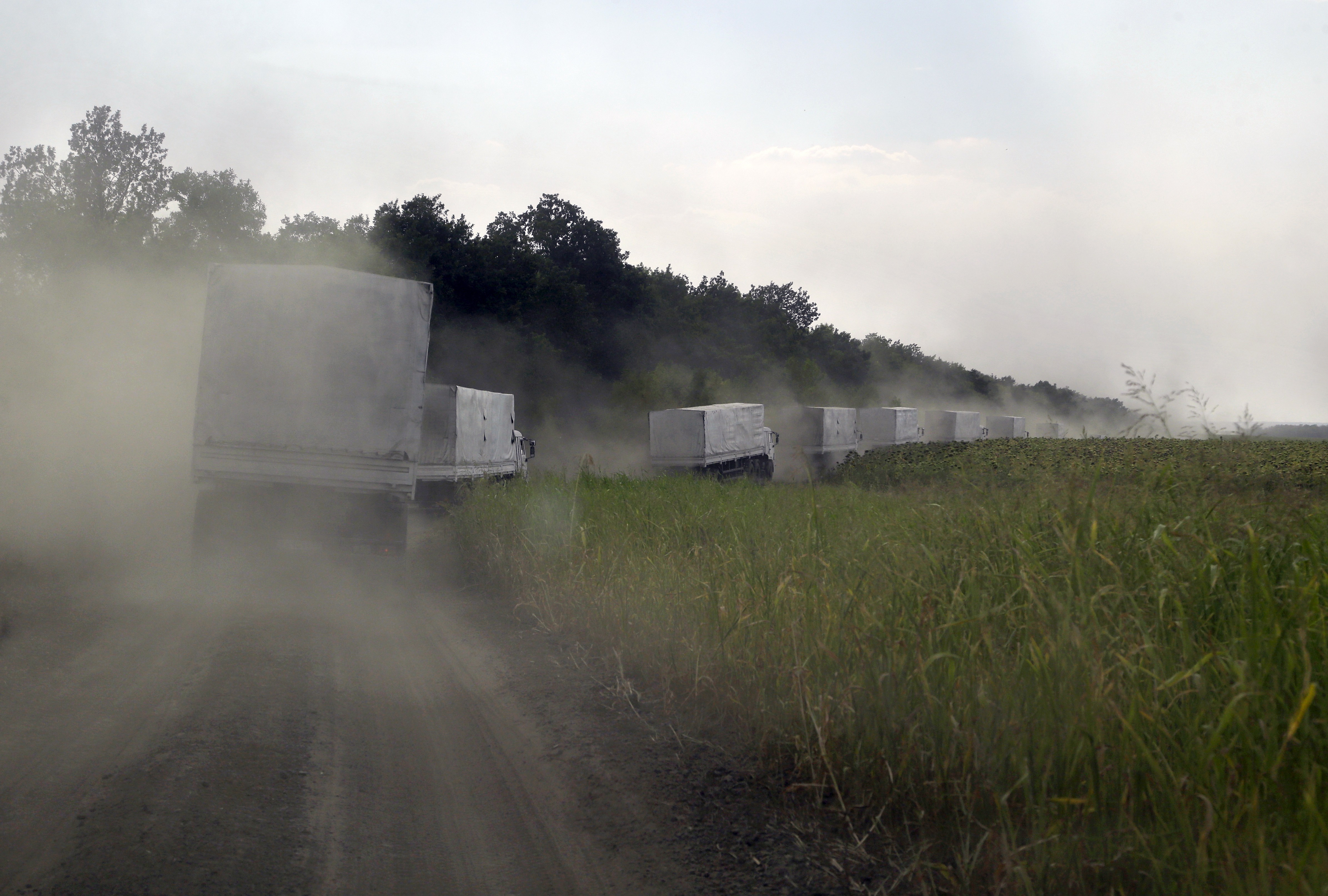 Russian aid convoy trucks roll along the main road to Luhansk after passing the eastern Ukrainian border post at Izvaryne on Friday. | AP