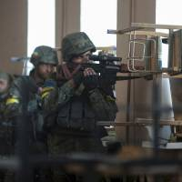Ukrainian servicemen take position during fighting with pro-Russian separatists in the eastern Ukrainian town of Ilovaysk on Tuesday. | REUTERS