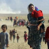 Displaced people from the minority Yazidi sect, fleeing violence from forces loyal to the Islamic State, walk toward the Syrian border near the town of Elierbeh of Al-Hasakah on Monday. | REUTERS