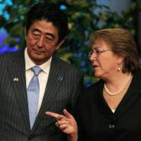 Prime Minister Shinzo Abe leans in to listen to Chilean President Michelle Bachelet as they wait for their staff to exchange folders, after each leader delivered a statement, at  the La Moneda presidential palace, in Santiago on Thursday. | AP