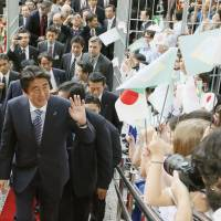 Prime Minister Shinzo Abe is welcomed at a party Saturday in Sao Paulo organized by a Japanese-Brazilian organization. | KYODO