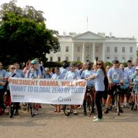 Anti-nuclear cyclists hold a banner urging U.S. President Barack Obama to abolish nuclear weapons by 2030, in Washington on Saturday, to coincide with the 69th anniversary of the U.S. atomic bombing of Nagasaki. | KYODO