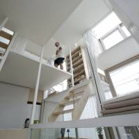 Sou Fujimoto's assistant walks inside the architect's house of glass in Tokyo on June 23. | AP