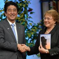 Prime Minister Shinzo Abe and Chilean President Michelle Bachelet pose for photos during a news conference at the Moneda Presidential Palace in Santiago on Thursday. | AFP-JIJI