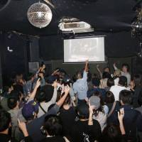 People dance at a special free event held in a former dance club in Osaka last October. | KYODO