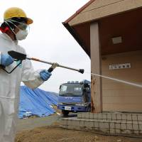 A worker uses a pressure hose in an attempt to wash radioactive particles off the exterior of a kindergarten in Minamisoma, about 20 km away from the severely damaged Fukushima No. 1 nuclear power plant, in August 2011. | AP