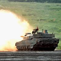 A Ground Self-Defense Force Type-10 tank fires live ammunition during a drill in Gotenba, Shizuoka Prefecture, on Sunday. | KYODO