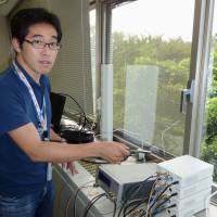 Seiji Kawamura, senior researcher at the National Institute of Information and Communications Technology in Koganei, western Tokyo, explains about a prototype system to receive radio waves for terrestrial digital broadcasting from the Tokyo Skytree broadcasting tower to forecast localized torrential downpours. | KYODO