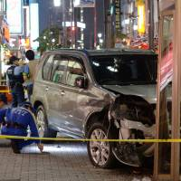 Police investigate the scene of a car crash in the Ikebukuro district of Tokyo on June 25. The driver, who was under the influence of legal 'loophole drugs,' killed one pedestrian and injured seven others. | KYODO