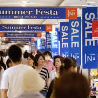 Shoppers walk through a mall in Tokyo in late June. A Kyodo survey of 106 major companies in Japan has found 100 expect the economy to expand toward the end of the year.   BLOOMBERG
