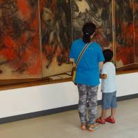 A mother and son view a painting on a folding screen depicting the horrors of the 1945 atomic bombings of Hiroshima and Nagasaki at the Maruki Gallery for the Hiroshima Panels in Higashimatsuyama, Saitama Prefecture, on Aug. 14. | KYODO