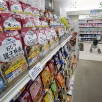 A shopper walks past a shelf stocked with Kewpie Corp.'s ready-to-eat 'nursing care food' packages at an Ito-Yokado supermarket in Tokyo on Aug. 5. | REUTERS