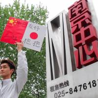 Koichi Kuwabara holds up a sign promoting Sino-Japanese friendship in the city of Nanjing, China, during his Free Hug campaign in April. | COURTESY OF KOICHI KUWABARA