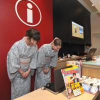 Alia Carter (left) from the United States and Paloma Free from Spain welcome foreign tourists at Coredo Muromachi's information counter in Tokyo's Nihonbashi district on July 19. | YOSHIAKI MIURA