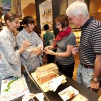 Carter and Free explain dried bonito products to two American tourists. | YOSHIAKI MIURA