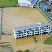 Kamodani Junior High School lies flooded after the Nakagawa River overflowed in Anan, Tokushima Prefecture, on Sunday. | KYODO