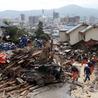 Rescue workers remove debris Tuesday to search for missing people at the site of a landslide six days after the disaster hit a residential area in the city. The death toll from the massive slides stands at 66 and 21 people remain missing. | AFP-JIJI