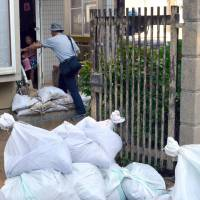 A man climbs over sandbags in front of his front door Sunday in the city of Hiroshima after the partial lifting of evacuation advisories allowed some residents to return. | KYODO