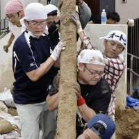 Volunteers clear debris Saturday morning from a residential area in Asaminami Ward, Hiroshima, that was devastated by mudslides last week. | KYODO