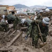 Self-Defense Force soldiers continue searching for survivors at a site where a landslide swept through a residential area in Asaminami Ward, Hiroshima, on Friday. | REUTERS
