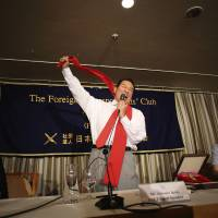 Antonio Inoki shouts to show his fighting spirit at the end of a news conference at the Foreign Correspondents' Club of Japan in Tokyo, on Thursday. | AP