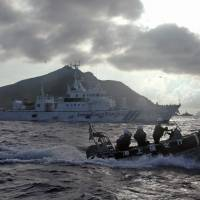 Japan Coast Guard vessels patrol the Senkakus, claimed by China as Diaoyu, last August. Tokyo on Friday gave names to five more of the uninhabited islets in the East China Sea chain. | AP