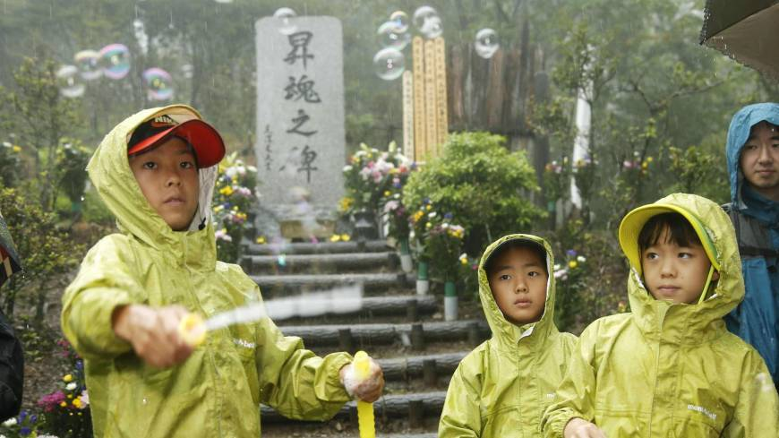 Children release bubbles Tuesday at a monument on Osutaka Ridge in Gunma Prefecture where JAL Flight 123 crashed. Mourners trekked there in heavy rain on the 29th anniversary of the accident.