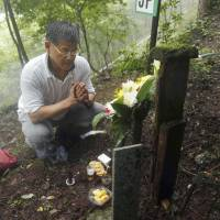 Masayuki Teranishi, 52, who lost his younger brother, Masatsugu, when Japan Airlines Flight 123 went down on Aug. 12, 1985, prays on a hillside at the crash site in Gunma Prefecture on Tuesday, the 29th anniversary of the world's worst single-plane disaster, which claimed 520 lives.  | KYODO