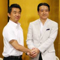 Nippon Ishin no Kai (Japan Restoration Party) leader Toru Hashimoto (left) and Kenji Eda, head of Yui no To (Unity Party), clasp hands during a meeting at a Nagoya hotel earlier this month. | KYODO