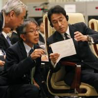 Foreign Minister Fumio Kishida talks with his delegates during the ASEAN Plus Three foreign ministers' meeting at the Myanmar International Convention Center in Naypyitaw on Saturday. | REUTERS