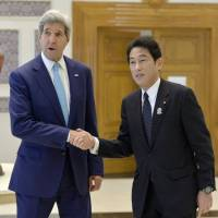 Foreign Minister Fumio Kishida and U.S. Secretary of State John Kerry shake hands in Myanmar's capital, Naypyitaw, on Saturday, prior to their talks. The two met on the sidelines of the ASEAN Plus Three regional summit. | KYODO
