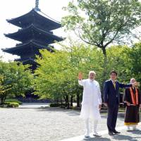 Indian Prime Minister Narendra Modi waves as he walks with his Japanese counterpart, Shinzo Abe, during a visit to Toji Temple in Kyoto on Sunday. | AFP-JIJI