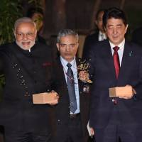 Indian Premier Narendra Modi and Prime Minister Shinzo Abe feed carp in the garden pond of the Kyoto State Guest House on Saturday. | POOL/AFP-JIJI