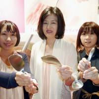 Noriko Ishiwata (center) and her colleagues at household goods maker Aux Co. show off some of the inventive new kitchen utensils they developed. | KYODO